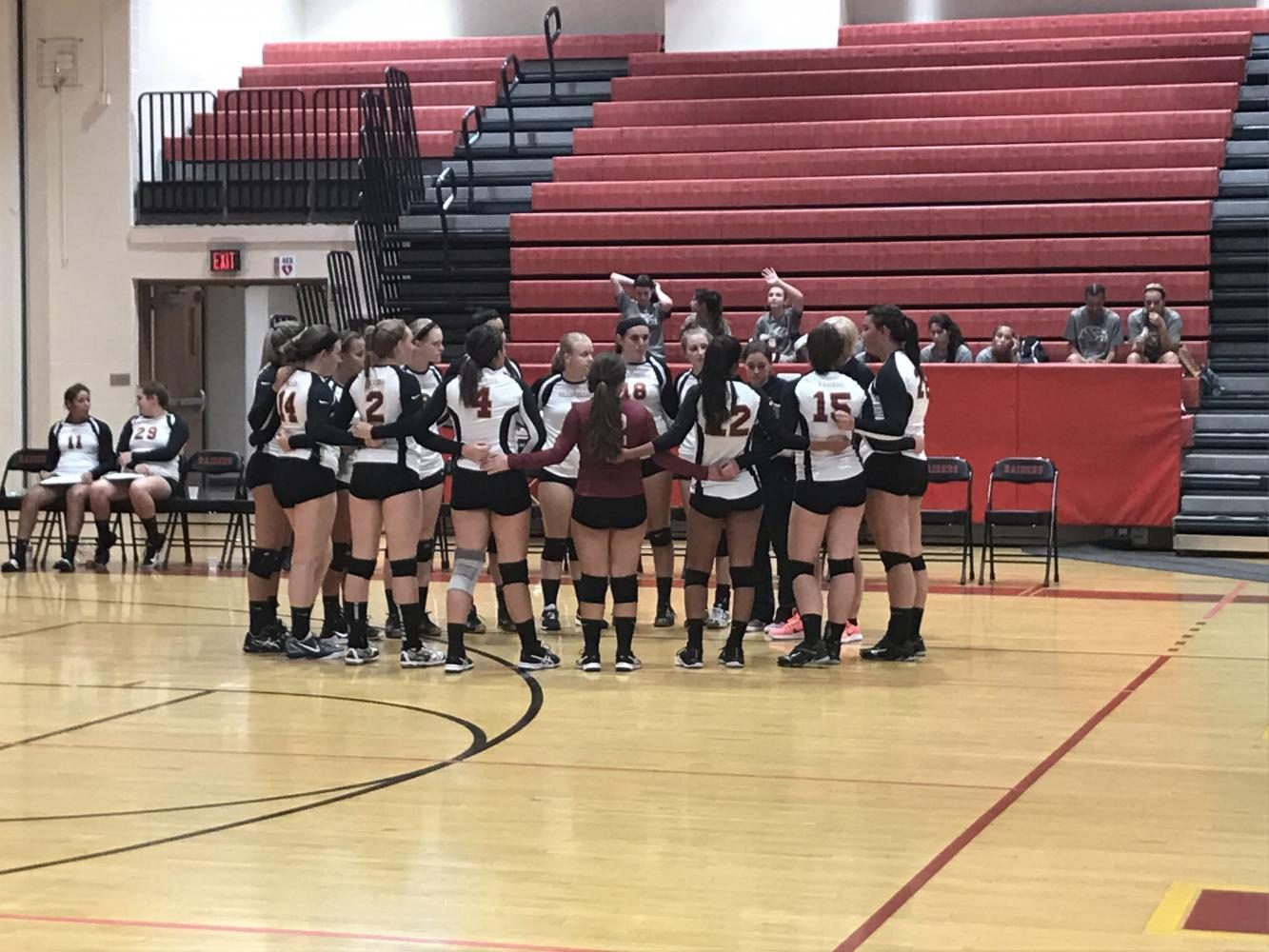 The volleyball team pays close attention as head coach Cheryl Iaione talks to them before a match.