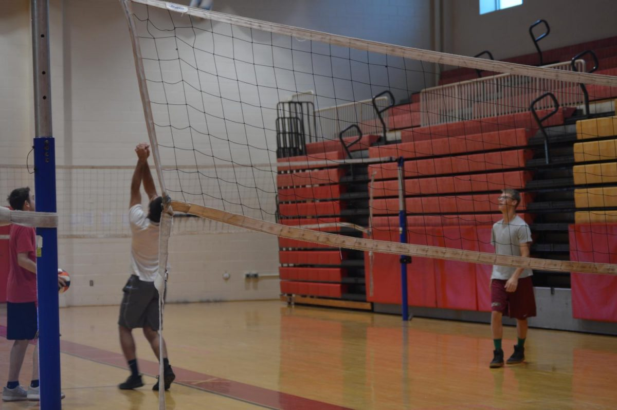 Senior Michael  Dooley prepares to send the ball over the net in gym class. Dooley and his fellow Raiders are still adjusting to the new gym policy rolled out this year.