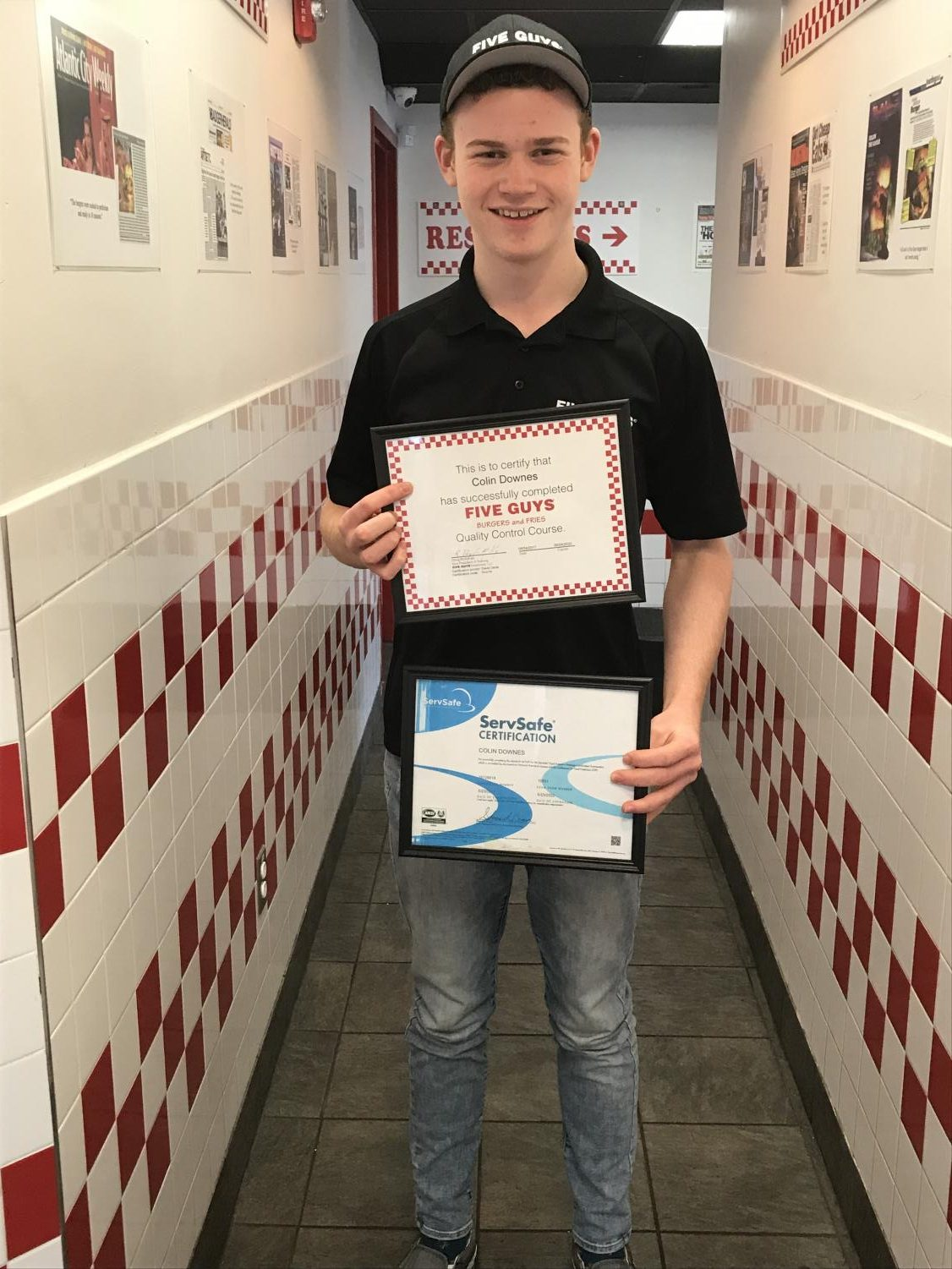 Senior Colin Downes shows off his certifications that help grant him the opportunity to be a manager at Five Guys.