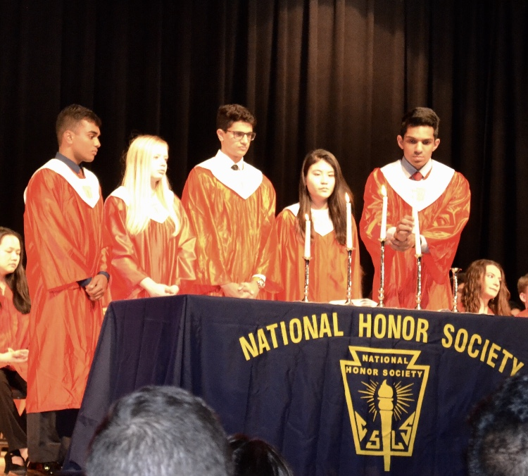 From left to right, seniors Rohil Chada, Kaley Murday, Karan Mahesh, Catherine Nguyen, and Rakesh Senthilvelan light the candles representing the pillars of the National Honor Society.