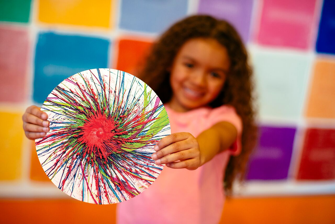 A visitor to the Crayola Experience shows off her spin art project!