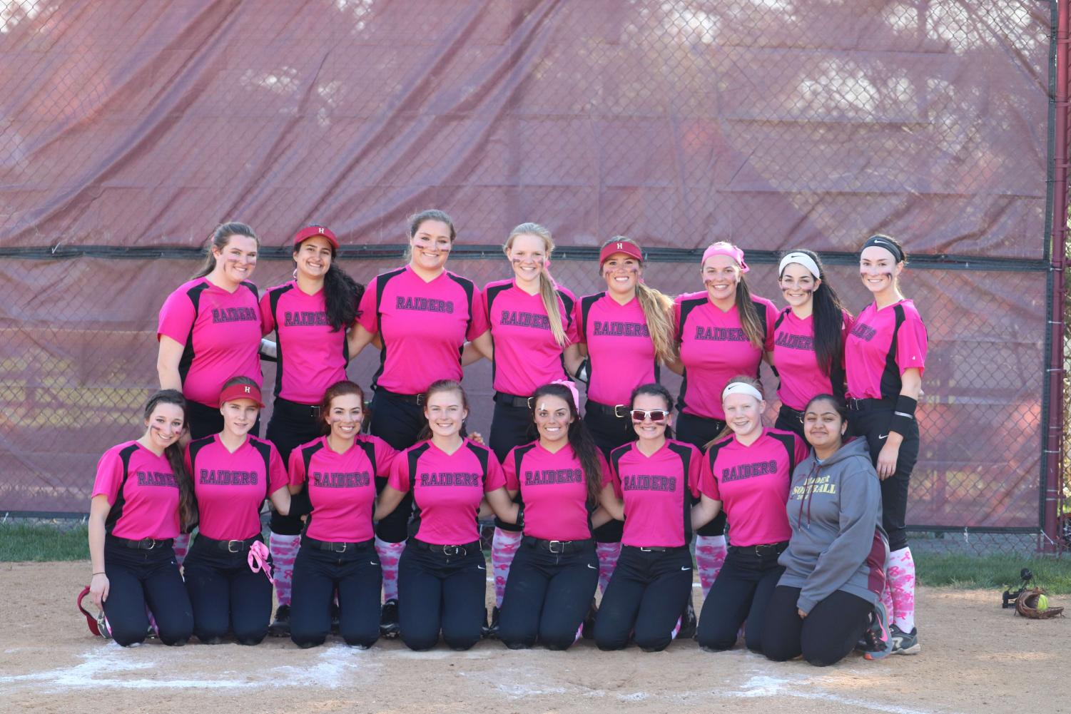 Hillsborough softball team poses before a game sporting their breast cancer awareness jerseys.