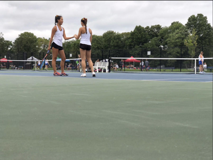 Seniors Hanna Kim and Cynthia Puleo celebrate winning a point in a recent doubles match.