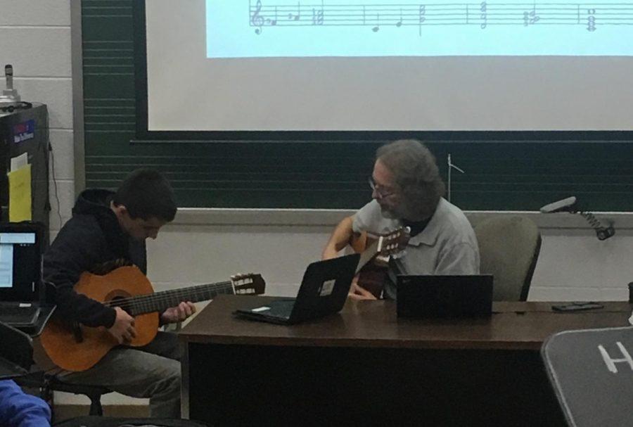 Music+teacher+Jonathan+Klizas+instructs+senior+Gavin+Tyman+on+the+guitar.