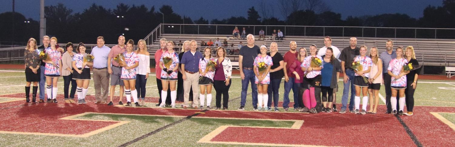 The seniors lined up before the game with their parents on Senior Night.