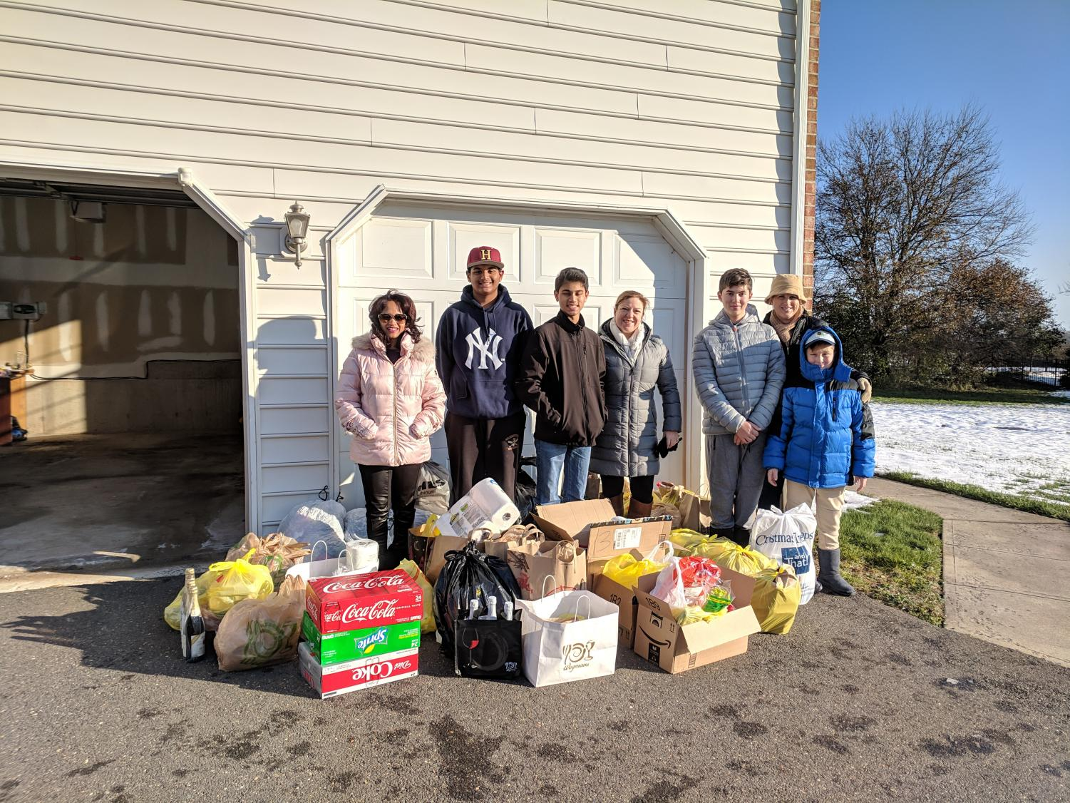 Aruna Dontabhaktuni, Tejas Patel, Miraj Vakil, Eileen Candelaria, Dean Milano, Robert Milano, and Devon Milano stand behind the food collected to be donated to families in need.