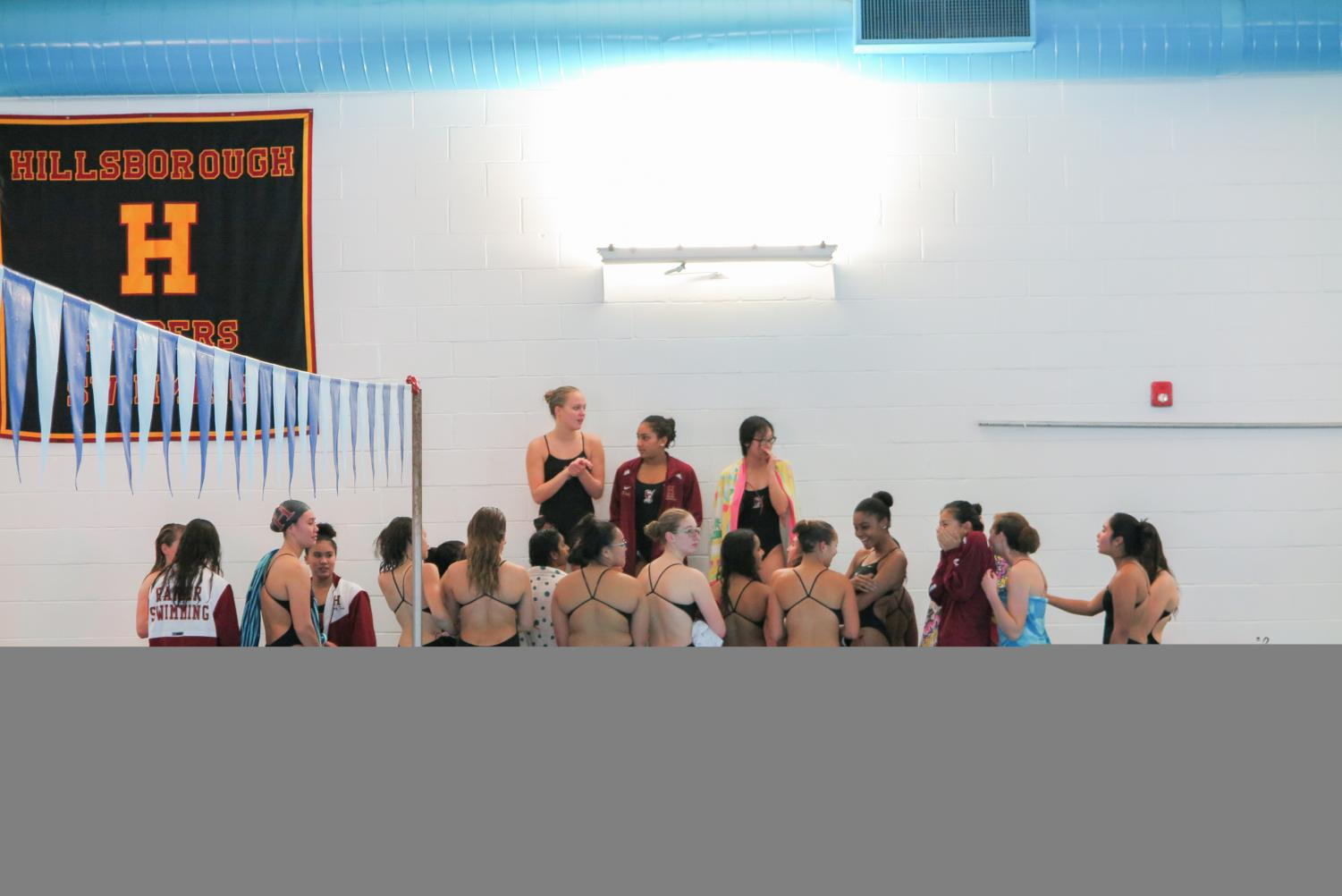 Seniors Jordan McChesney, Sankya Parvatrao, and Nicole Zou give the team a speech before the meet against Mount Saint Mary on Dec. 6..