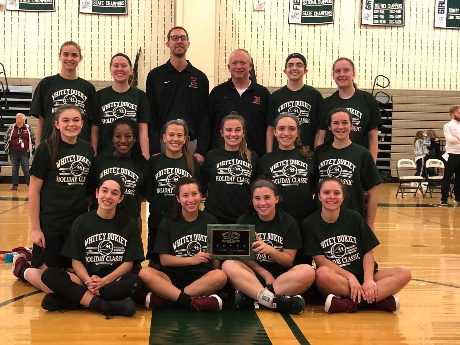 The Lady Raiders and head coach Ian Progin pose with their well-deserved championship hardware after winning the holiday tournament.