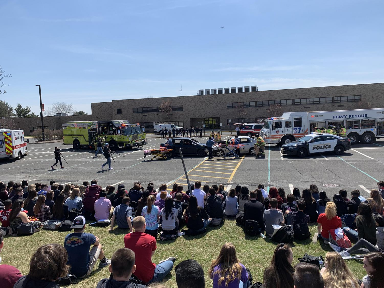 Students gather to observe the chilling staged accident scene.