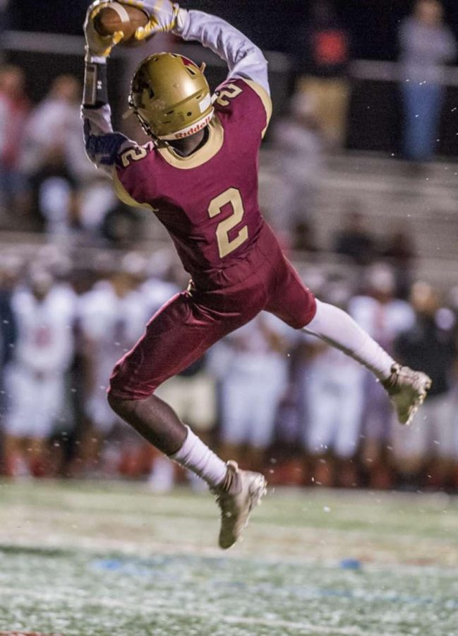 Sophomore Thomas Amankwaa leaps into the air to get his second interception of the night.