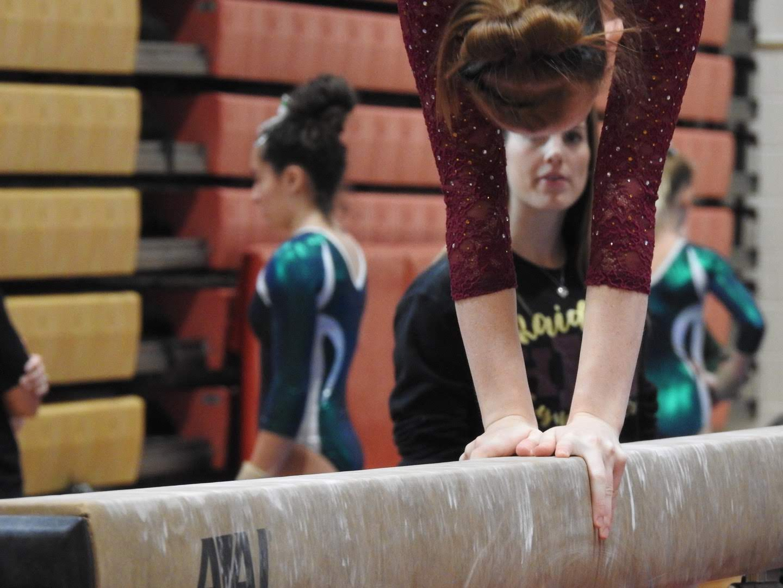 Junior Meghan Kurz, performing her balance beam routine.