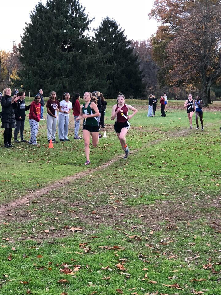 Senior Bridget Esposito tries to beat out her competitors as her teammates cheer her on.