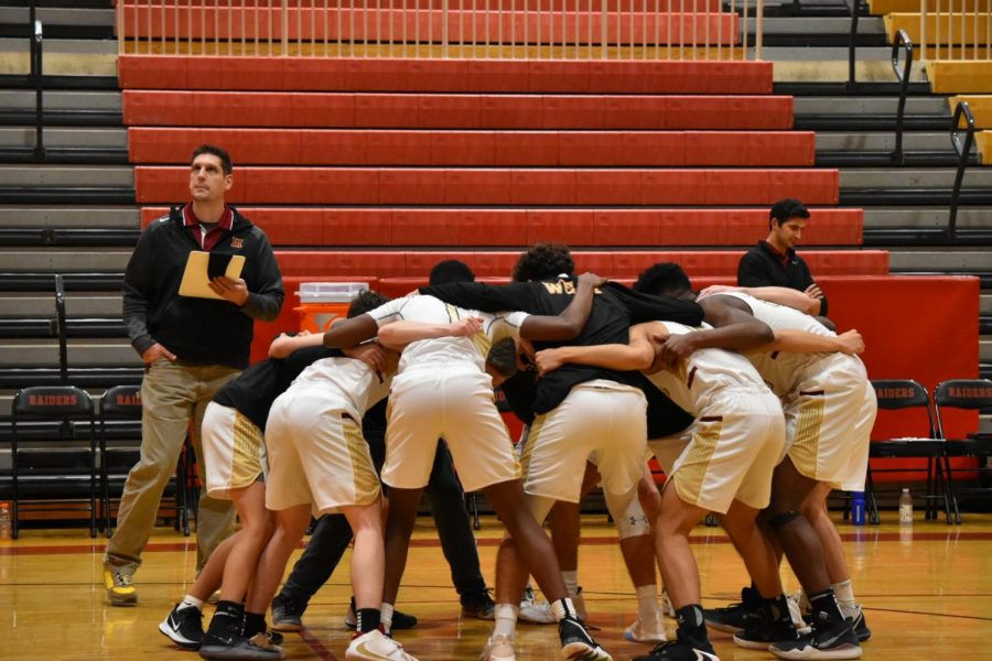 The+varsity+boys+basketball+team+huddles+before+battling+on+the+hardwood.
