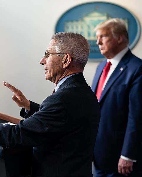 Dr. Anthony Fauci speaks beside President Trump at a White House press briefing.