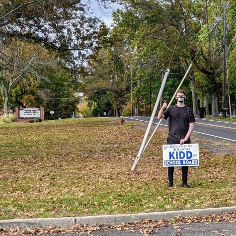 Senior Benjamin Kidd puts up one of his many signs outside of Sunnymead Elementary School, where he started his Hillsborough Education.