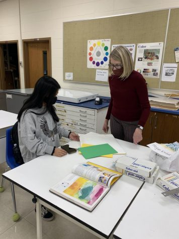Art teacher Lynn Mound doing what she does best, guiding a student to success.